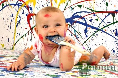 грязный малыш с кисточкой во рту