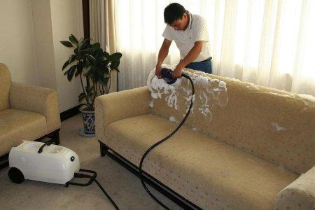 мужчина пылесосит мебель